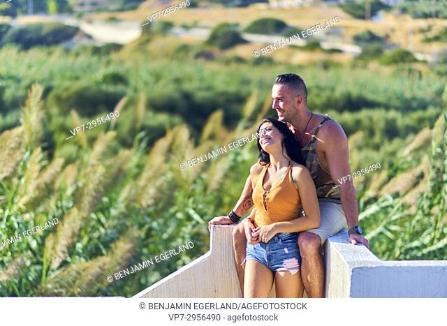 happy young couple leaning on wall in nature. Greek ethnicity. In holiday destination Hersonissos, Crete, Greece