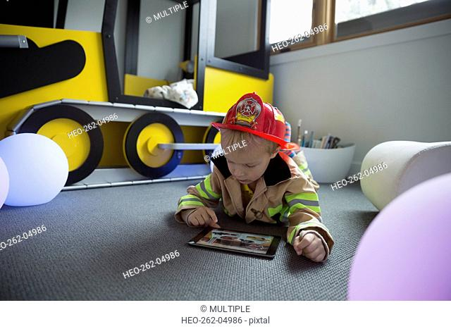Boy fireman costume using digital tablet floor