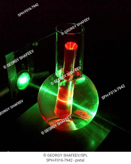 Laser and ruby rod. Experiment with a green laser beam being used to induce red luminescence in a rod of artificial ruby