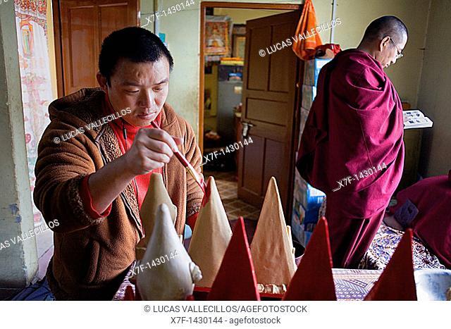 Monk making offerings, in Gaden Shartse monastery McLeod Ganj, Dharamsala, Himachal Pradesh state, India, Asia