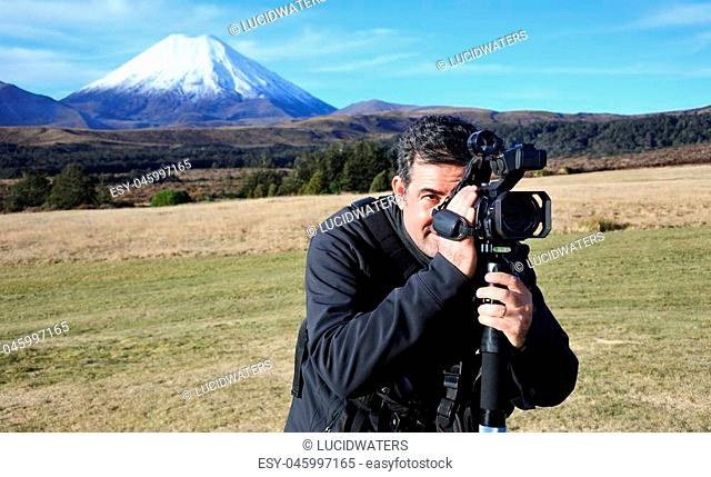 Professional nature, wildlife and travel videographer filming Mount Ngauruhoe outdoors during on location photo assignment in in Tongariro National Park New...