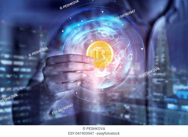 Hand holding abstract digital golden bitcoin on blurry city background. Cryptocurrency and e-commerce concept. Double exposure