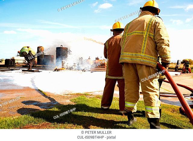 Firemen training, team of firemen spraying firefighting foam at training facility