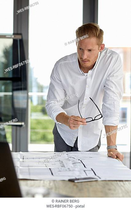 Young man working on blueprint on desk in office