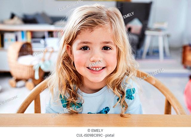 Portrait of young girl, sitting at table, smiling