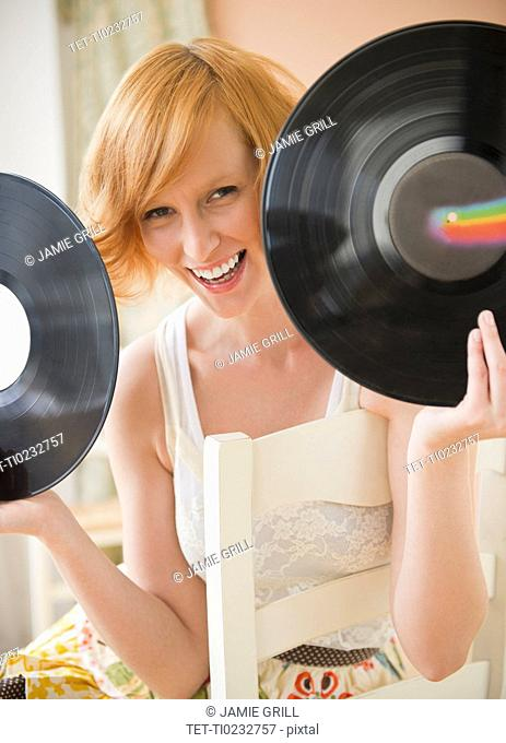 Portrait of young woman holding vinyl records