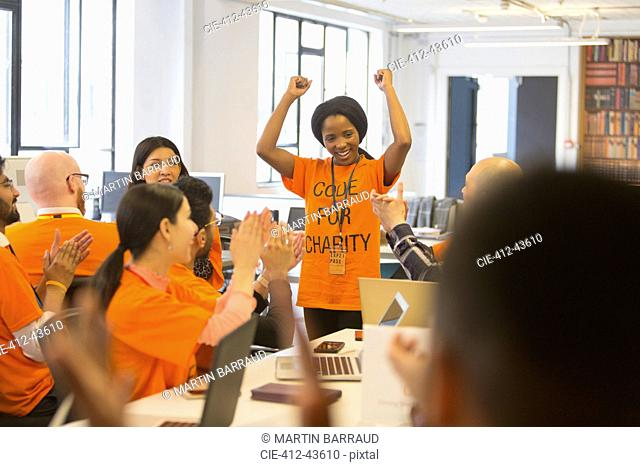 Happy hackers cheering for woman, coding for charity at hackathon