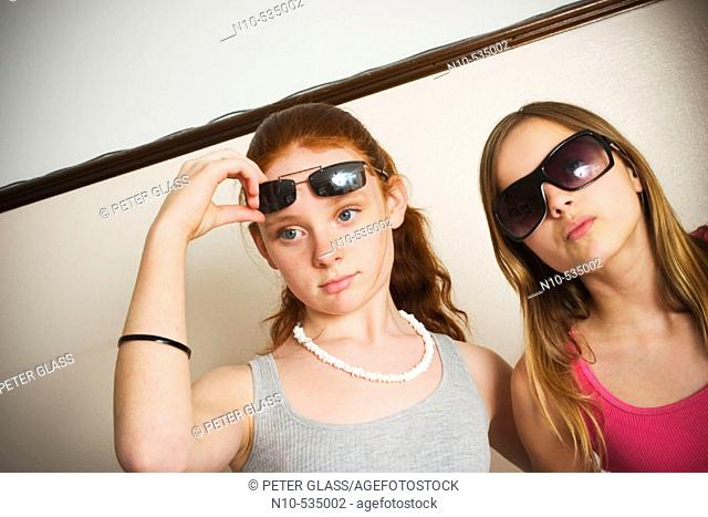 Long red-hair and blond-hair teen girls, both wearing sunglasses, clowning around together