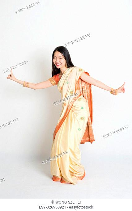 Portrait of young mixed race Indian Chinese girl in traditional sari dress dancing, full length on plain background