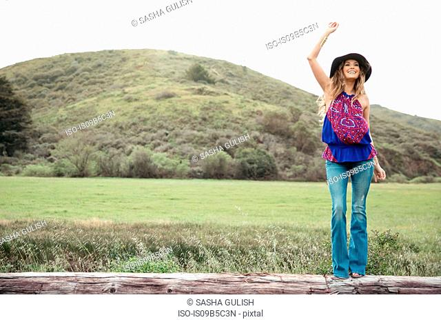 Boho style young woman waving from log
