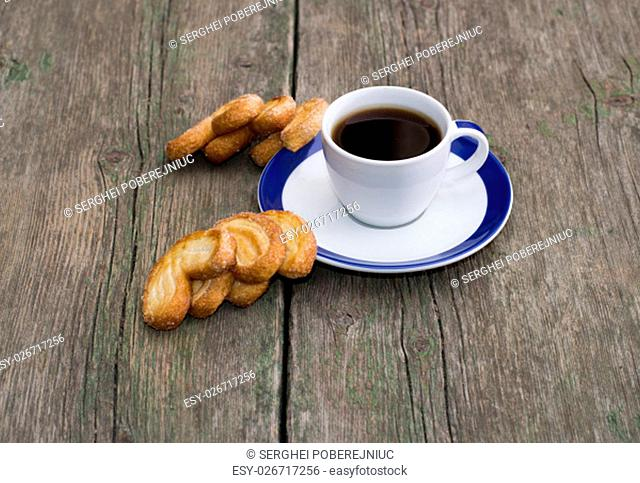 cup of coffee and two groups of cookies on a wooden table, a still life on a subject food and drinks