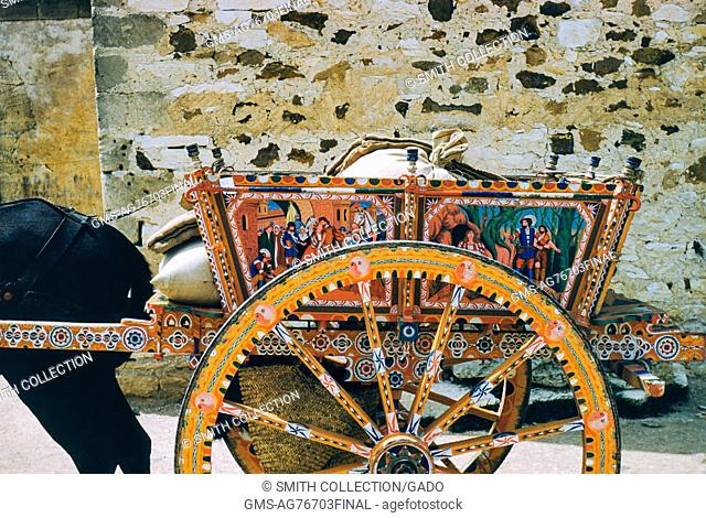Detail view of a horse-drawn cart with ornate painted biblical scenes, with a stone wall in the background, Italy, 1952