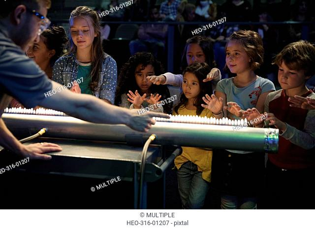 Children and scientist creating acoustic waves using a Rubens tube in science center theater
