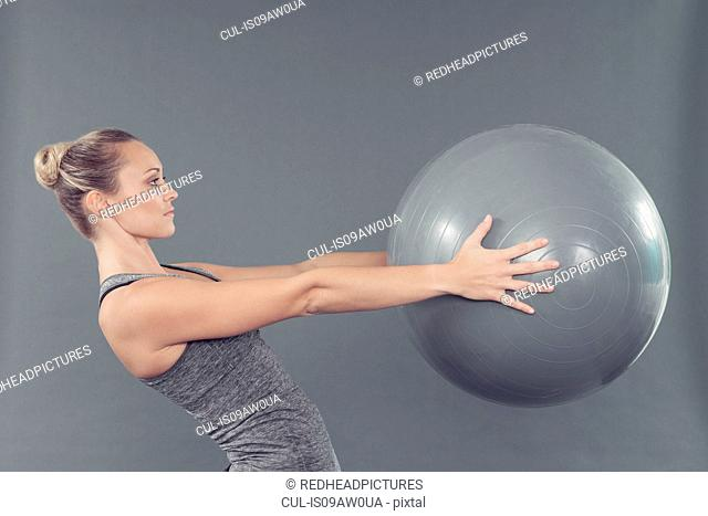 Young woman working out with gym ball, grey background