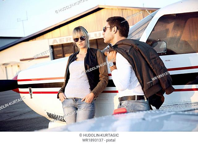 Young couple standing by propeller airplane
