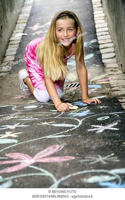 portrait of young girl painting with crayons in the street