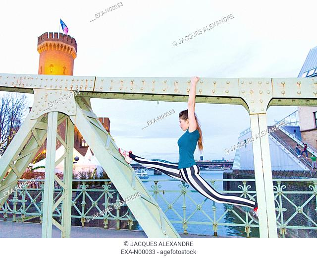 woman doing urban yoga exercises on a bridge at night with the Rhine river in the background