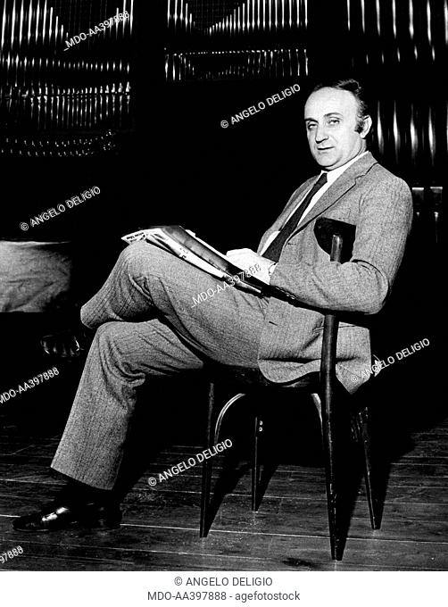 Raoul Grassilli sitting in front of a pipe organ. Italian actor and director Raoul Grassilli sitting on a wooden chair in front of a pipe organ