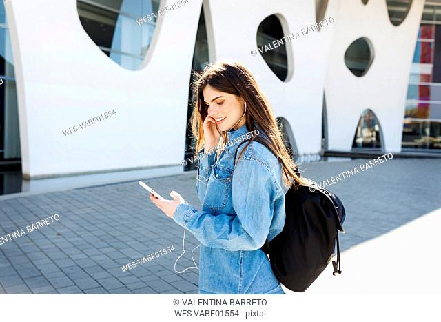 Spain, Barcelona, smiling young woman with backpack listening music with cell phone and earphones