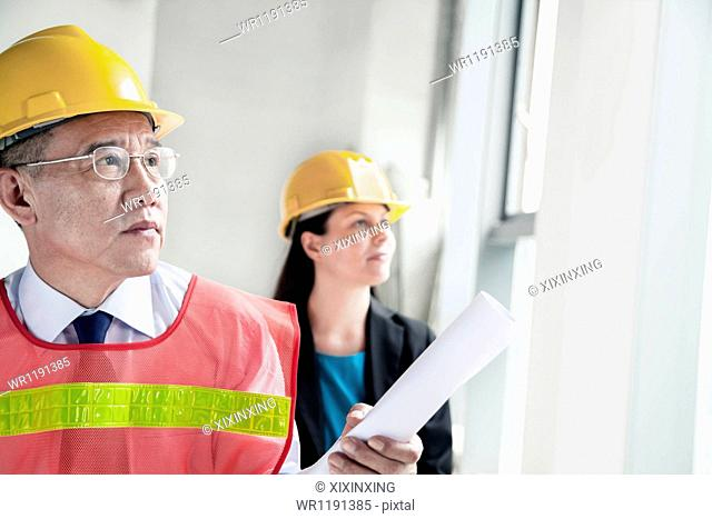 Two architects in protective workwear and hardhats working in an office building