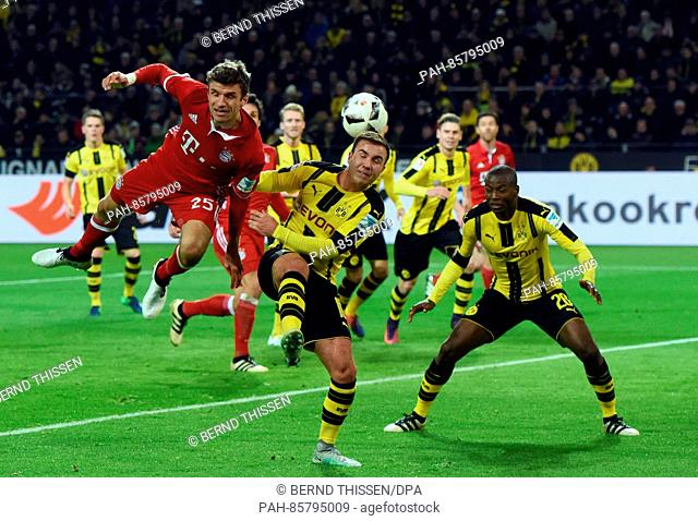 Bayern's Thomas Mueller and Dortmund's Mario Goetze (c) and Adrian Ramos in action during the Bundesliga soccer match between Borussia Dortmund and Bayern...