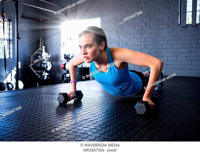 Fitness woman making fitness exercises in a gym with flare