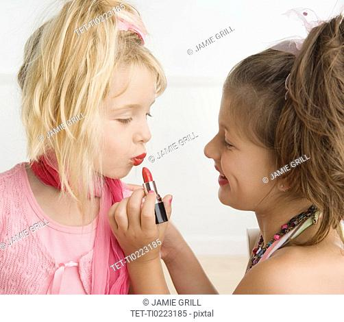 Girl putting lipstick on sister