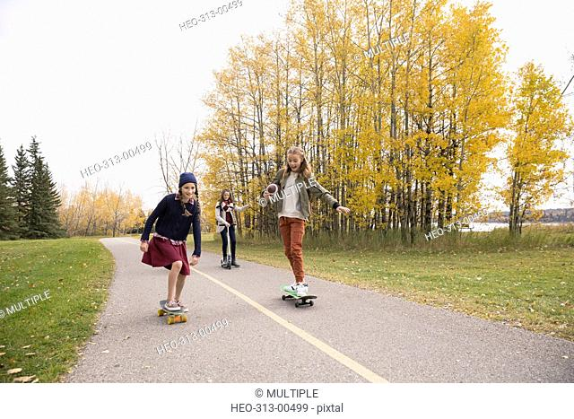 Tween girls skateboarding on autumn park path