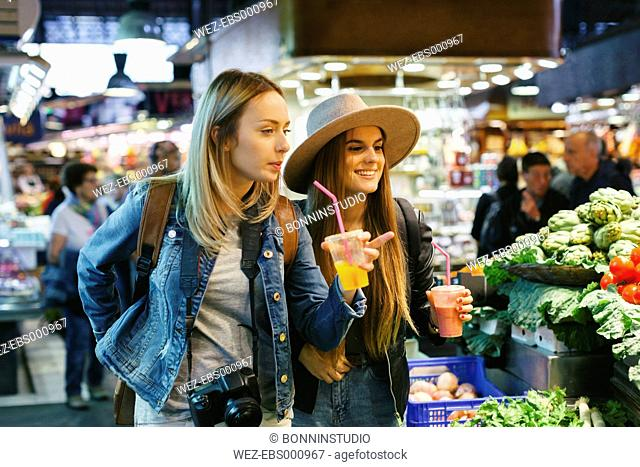 Two young women drinking smoothies on a market