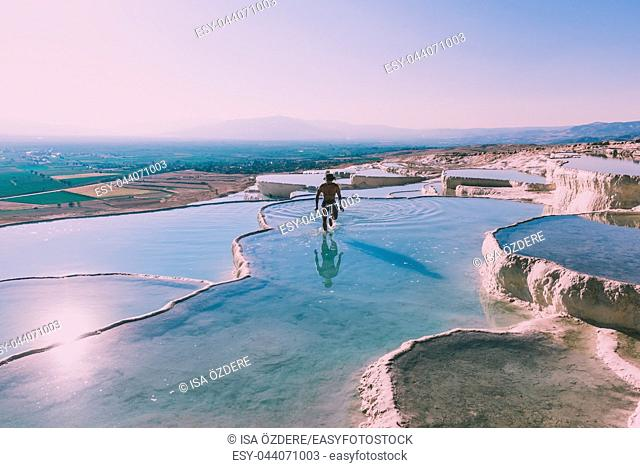 Unidentified man walks at Pamukkale (Cotton Castle) that is popular with Travertine pools and terraces where people love to visit in Pamukkale, Turkey