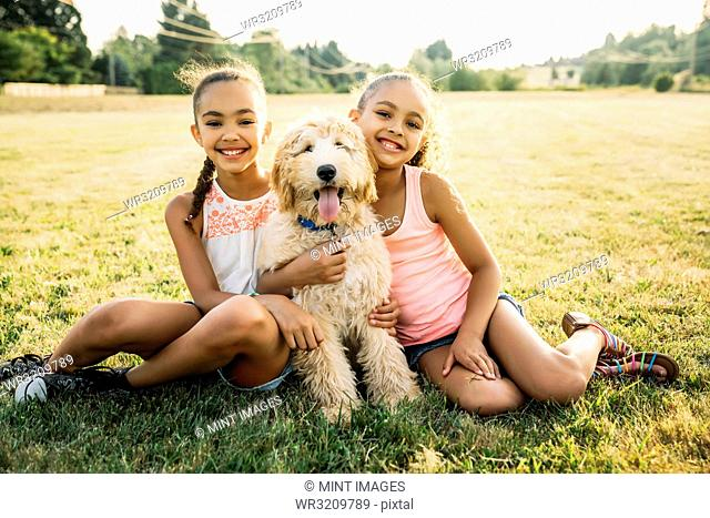 Portrait of smiling happy girls hugging labradoodle puppy in park