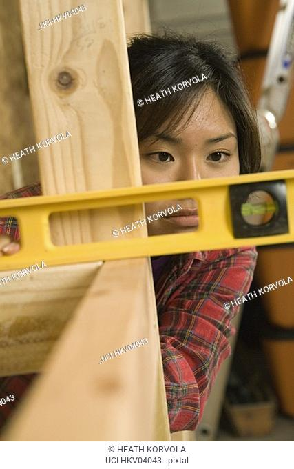 Teenage girl measuring wood with level