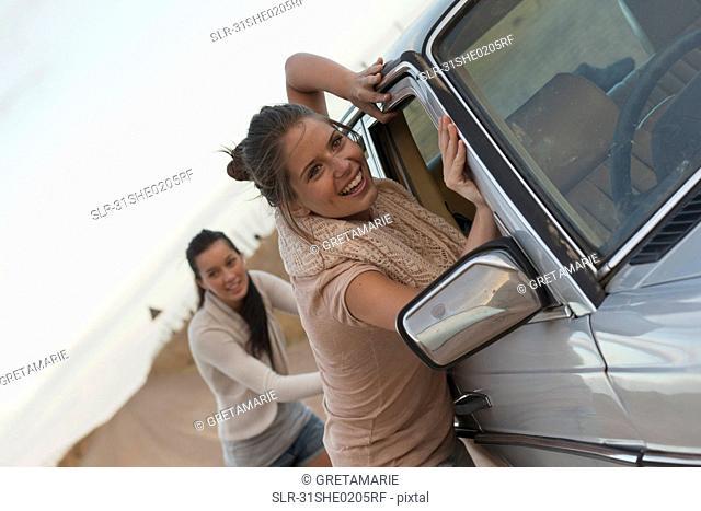 Girls pushing car