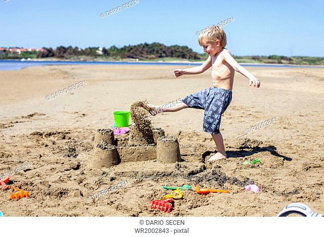 Boy kicking against sandcastle on beach