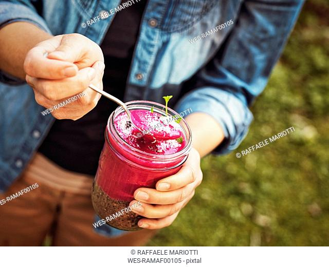 Woman's hands holding glass of rhubarb and chia seeds dessert with dark chocolate nibs