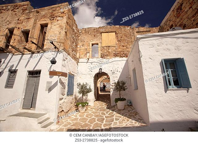 Tourist walking through the passageway of the Kastro or Castle in the old town Chora or Chorio, Kimolos, Cyclades Islands, Greek Islands, Greece, Europe
