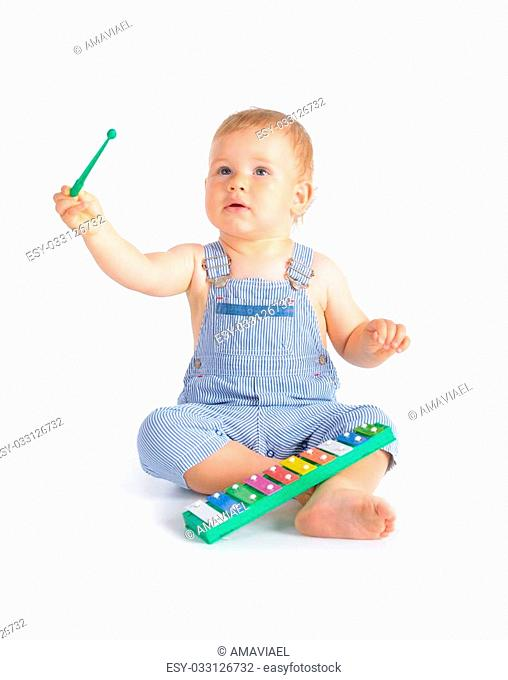 Cheerful baby boy playing on xylophone isolated over white background