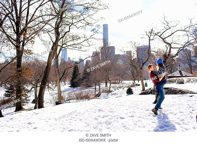 Romantic young couple having fun in snowy Central Park, New York, USA