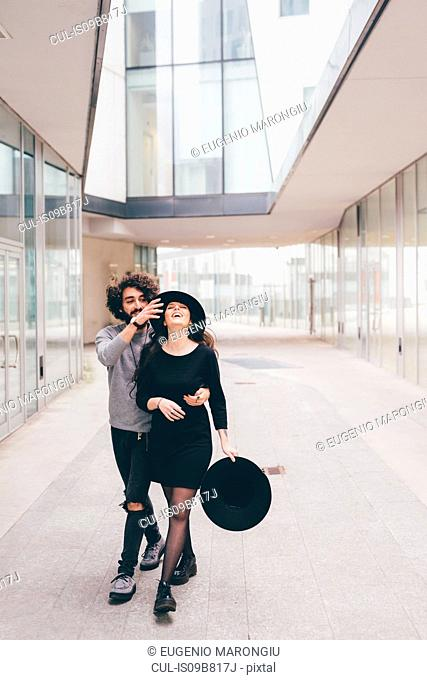 Young couple walking in urban environment, fooling around, laughing