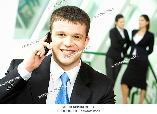 Portrait of a young successful businessman making business call on mobile looking at camera on the background of two standing women