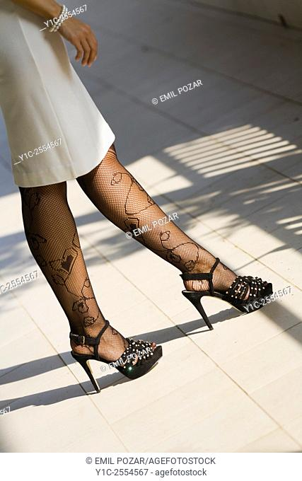 Legs only dress and high-heels walking on street