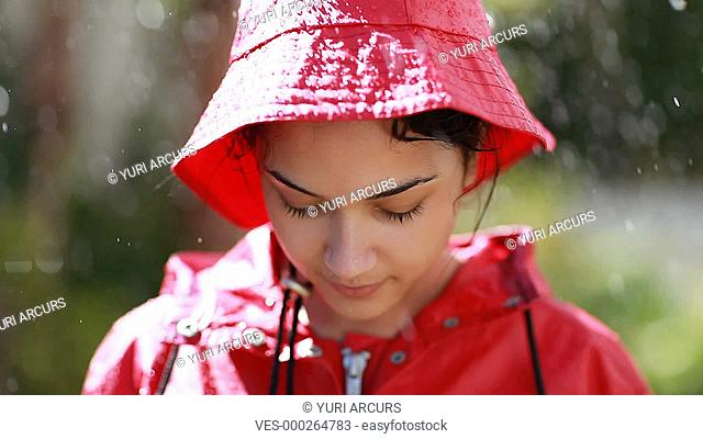 Sweet young teenager wearing a red raincoat and standing in the rain with a smile