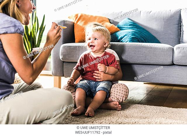 Mother feeding kids in living room