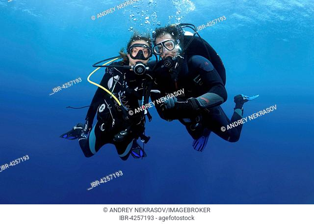 Couple, divers in the water holding hands, Indian Ocean, Maldives