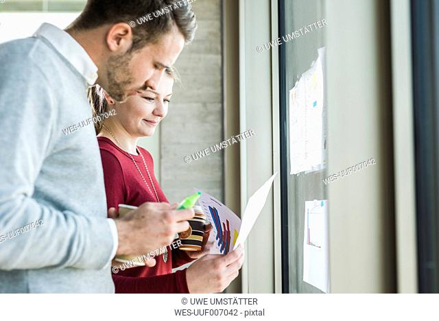 Two colleagues at office window looking at paper