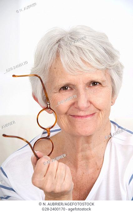 Portrait of beautiful senior woman holding glasses