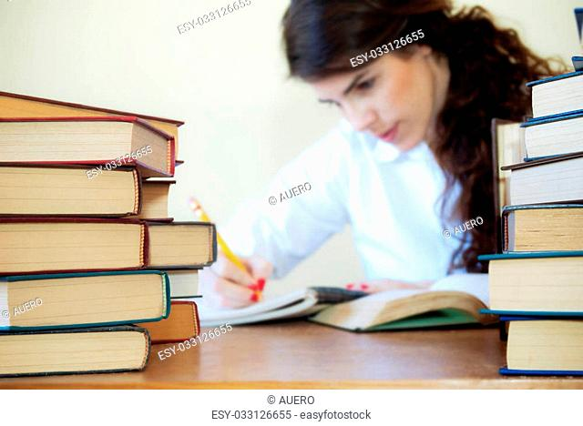 Young woman studying with a lot of books