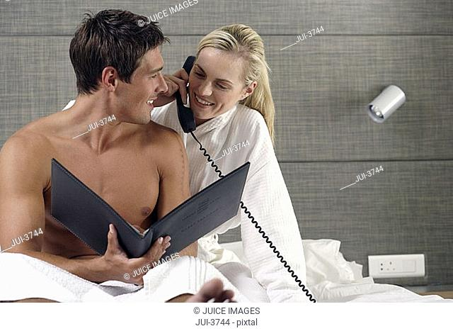 Couple relaxing on hotel bed, woman using telephone, ordering room service, smiling