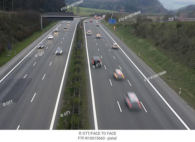 Vehicles seen speeding across the highway with trees and grass on either side