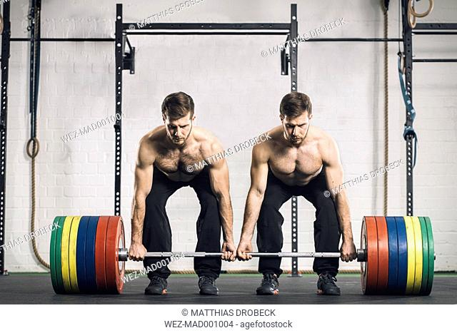 Twin brothers weightlifting in gym